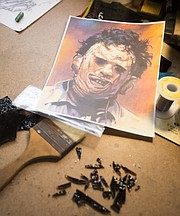 A portrait of Leatherface sits on the desk of his studio as Niswonger works to cut glass pieces to make the killer's hair.