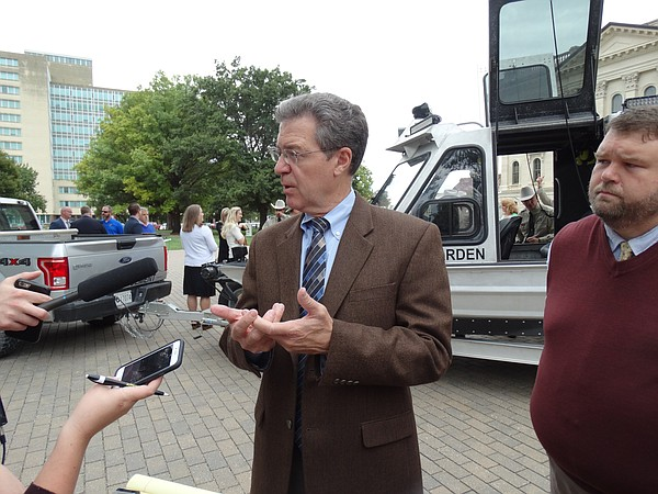 Gov. Sam Brownback speaks with reporters outside the Kansas Statehouse.