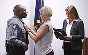 Lawrence police chief Gregory Burns Jr. has his badge pinned on by his wife following his swearing in ceremony on Monday, Oct. 2, 2017 at the Lawrence Police Department Investigations Center, 4820 Bob Billings Parkway. Burns formerly served as the assistant police chief in the Louisville, Ky., Metro Police Department. At right is Lawrence city clerk Sherri Riedemann, who performed Burns' swearing in.