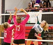 Free State sophomore Haley Hippe prepares for a spike over the top of Lawrence High's blockers, Baylee Unruh (12) and Sammy Williams (17), during Tuesday's triangular at LHS.