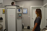 Journal-World health reporter Mackenzie Clark, left, is shown inside the cryosauna at Optimal Wellness and Cryospa as general manager Tashina Case stands by.