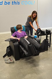 Tashina Case, general manager of Optimal Wellness and Cryospa, adjusts NormaTec settings for Journal-World health reporter Mackenzie Clark.