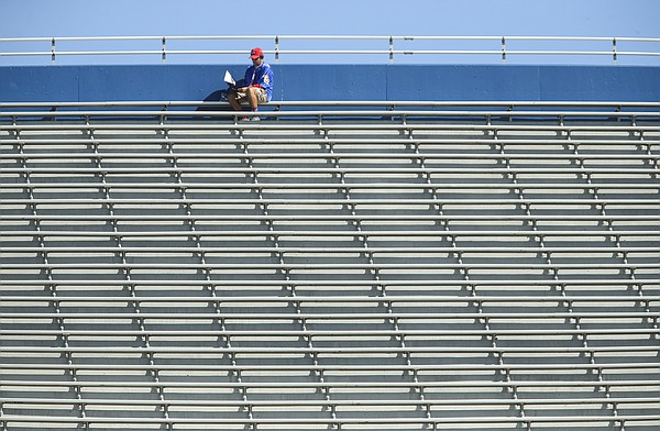 A Kansas fan looks through the game program from the top of the stands during the fourth quarter of KU's football game against Texas Tech, Saturday, Oct. 7, 2017 at Memorial Stadium. The Jayhawks lost, 65-19.