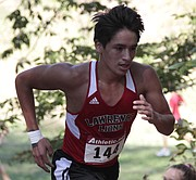 Lawrence High senior Carson Jumping Eagle runs up Cemetery Hill on Friday at Rim Rock Farm during the Sunflower League cross country meet.