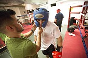 Corrections Officer Jesse Cheek has his head gear tightened by trainer Daniel Barajas on Thursday, Oct. 12, 2017 at The Summit, 901 New Hampshire St.