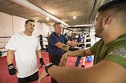 Sheriff's Department Corrections Officer Jesse Cheek and his father, Lt. Randall Cheek, talk with their coach Daniel Barajas before sparring on Thursday, Oct. 12, 2017 at The Summit, 901 New Hampshire St.