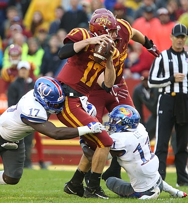 Kansas defensive end Josh Ehambe (17) and Kansas safety Mike Lee (11) bring down Iowa State quarterback Kyle Kempt (17) for a sack during the second quarter on Saturday, Oct. 14, 2017 at Jack Trice Stadium in Ames, Iowa.
