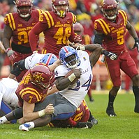 Kansas running back Taylor Martin (24) is wrestled to the ground by Iowa State linebacker Joel Lanning (7) during the third quarter on Saturday, Oct. 14, 2017 at Jack Trice Stadium in Ames, Iowa.