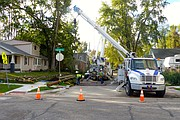 A Westar Energy crew replaces a downed transmission pole Sunday morning at Fourth and Locust streets. Saturday's storm caused widespread power outages in North Lawrence. Westar's online power outage map says the company would restore power to all customers by 11 p.m. Sunday.