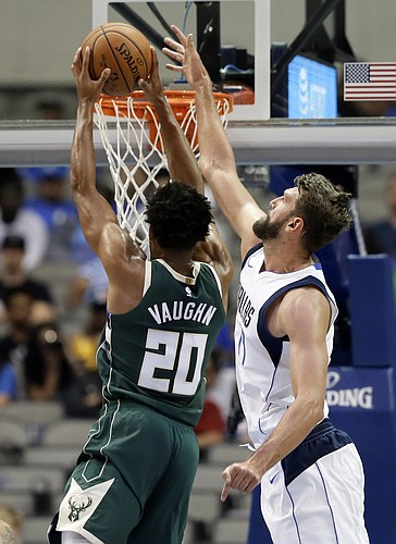 Milwaukee Bucks guard Rashad Vaughn (20) gets past Dallas Mavericks center Jeff Withey for a basket during the second half of a preseason NBA basketball game, Monday, Oct. 2, 2017, in Dallas. (AP Photo/Tony Gutierrez)
