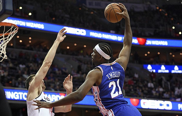 Philadelphia 76ers center Joel Embiid (21) goes to the basket against Washington Wizards forward Jason Smith, left, during the first half of an NBA basketball game, Wednesday, Oct. 18, 2017, in Washington. Smith was charged with a foul on the play.(AP Photo/Nick Wass)