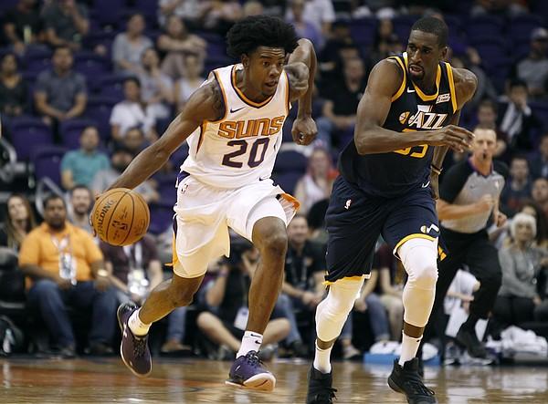 Phoenix Suns forward Josh Jackson (20) advances the ball up-court on a fast break as Utah Jazz forward Ekpe Udoh defends during the first half of a preseason NBA basketball game Monday, Oct. 9, 2017, in Phoenix. (AP Photo/Ralph Freso)