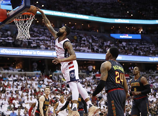 Washington Wizards forward Markieff Morris, left, dunks the ball while Atlanta Hawks forward Kent Bazemore, right, watches during the first half in Game 1 of a first-round NBA basketball playoff series, in Washington, Sunday, April 16, 2017. The Wizards won 114-107. (AP Photo/Manuel Balce Ceneta)