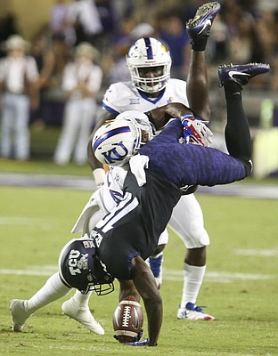 TCU wide receiver Jalen Reagor (18) is upended by Kansas safety Tyrone Miller Jr. (22) during the first quarter, Saturday, Oct. 21, 2017 at Amon G. Carter Stadium in Fort Worth.