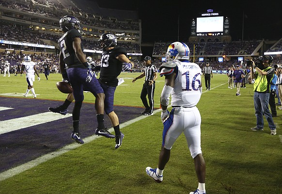 Kansas cornerback Kyle Mayberry (16) watches as TCU wide receiver Taj Williams (2) and TCU wide receiver Ty Slanina (13) celebrate Williams' touchdown catch during the third quarter, Saturday, Oct. 21, 2017 at Amon G. Carter Stadium in Fort Worth.