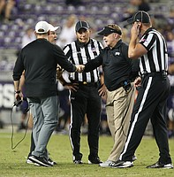 Kansas head coach David Beaty, left, and TCU head coach Gary Patterson bump fists during a meeting with game officials about a running clock the fourth quarter because of inclement weather approaching the stadium, Saturday, Oct. 21, 2017 at Amon G. Carter Stadium in Fort Worth.