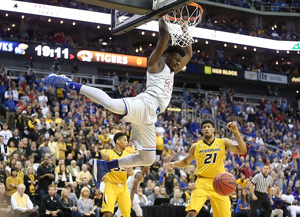 Kansas center Udoka Azubuike (35) finishes a lob dunk before Missouri forward Jordan Barnett (21) during the first half of the Showdown for Relief exhibition, Sunday, Oct. 22, 2017 at Sprint Center in Kansas City, Missouri.
