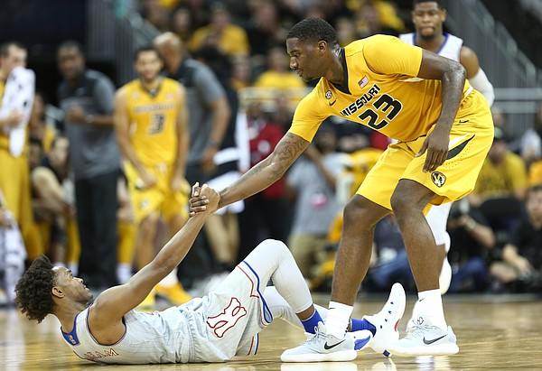 Missouri forward Jeremiah Tilmon (23) gives Kansas guard Devonte' Graham (4) a hand off the floor after fouling him during the second half of the Showdown for Relief exhibition, Sunday, Oct. 22, 2017 at Sprint Center in Kansas City, Missouri.