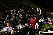 Head football coach Dirk Wedd goes over a play with members of the Lawrence High football team during a game against Blue Valley Northwest on Oct. 27, 2017. Wedd has been the head coach since 1999. Lawrence won 28-27.