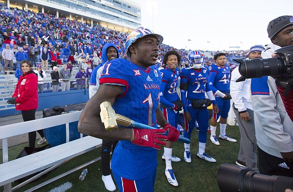 Kansas wide receiver Steven Sims Jr. (11) sports a work helmet and a sledge hammer to inspire his teammates after pulling in a deep touchdown pass during the fourth quarter on Saturday, Oct. 28, 2017 at Memorial Stadium.