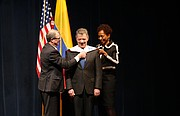 Chancellor Douglas Girod and former chancellor Bernadette Gray-Little perform the hooding ceremony on Colombian President Juan Manuel Santos at the Lied Center on Tuesday, Oct. 31, 2017. Santos graduated from the University of Kansas in 1973, and on Tuesday was presented an honorary Doctor of Humane Letters degree for outstanding contributions to achieving peace in his country and the world.