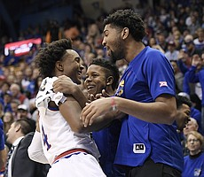 Kansas senior guard Devonte' Graham smiles with transfers Dedric Lawson and Charlie Moore after a missed chance by Mitch Lightfoot during an exhibition game Tuesday against Pittsburg State at Allen Fieldhouse.