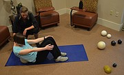 Becky Bridson, a Lawrence-based Yamuna body rolling practitioner, guides Journal-World health reporter Mackenzie Clark through rolling the right side of her back.