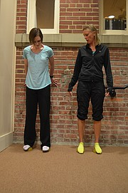 "Journal-World health reporter Mackenzie Clark, left, and Becky Bridson, a certified Yamuna body rolling practitioner, stand on the ""foot wakers,"" designed to release soft tissue in the feet and improve circulation, among other benefits."