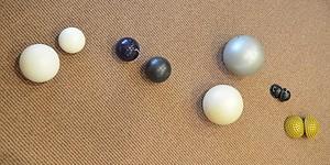 """Several of Becky Bridson&squot;s Yamuna balls sit on the floor of the Journal-World building. Third from the left is the purple ball, the smallest and most intense of the Yamuna balls. At the far right are the """"foot wakers."""""""