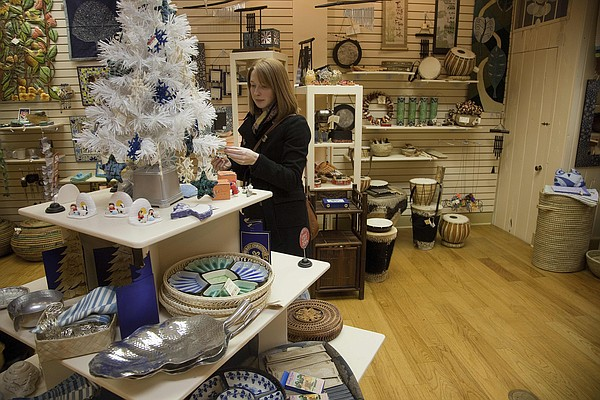 In this file photo from December 2012, Lawrence resident Kelsey Richardson looks over some of the fair trade items for sale at Ten Thousand Villages, 835 Massachusetts St.