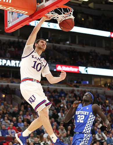 Kansas guard Sviatoslav Mykhailiuk (10) delivers a breakaway dunk before Kentucky forward Wenyen Gabriel (32) during the second half on Tuesday, Nov. 14, 2017 at United Center.