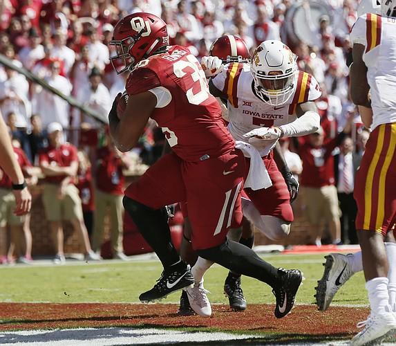Oklahoma fullback Dimitri Flowers (36) runs into the end zone with a touchdown in front of Iowa State's Joel Lanning (7) during an NCAA college football game in Norman, Okla., Saturday, Oct. 7, 2017. Iowa State won 38-31.