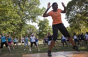 In this file photo from July 2012, Susan King, a fitness instructor with Lawrence Parks and Recreation, leads a group in a Zumba in the Park event amid triple-digit temperatures.
