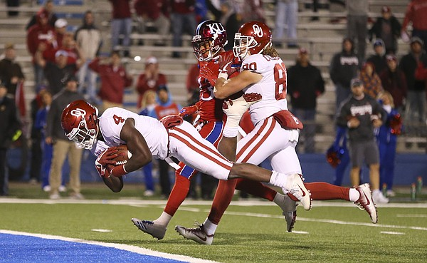 Kansas cornerback Hasan Defense (13) is pushed aside by Oklahoma tight end Grant Calcaterra (80) as Oklahoma running back Trey Sermon (4) dives into the end zone for a touchdown during the fourth quarter on Saturday, Nov. 18, 2017 at Memorial Stadium.