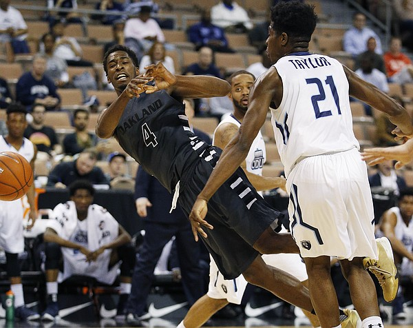 Oakland forward Jalen Hayes (4) falls while driving past Old Dominion forward Denzell Taylor during the first half of an NCAA college basketball game for the Vegas 16 championship, Wednesday, March 30, 2016, in Las Vegas.