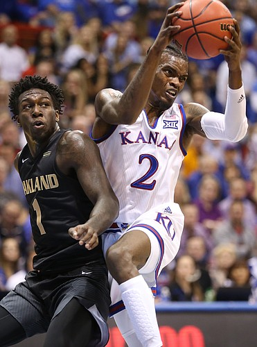 Kansas guard Lagerald Vick (2) looks to throw a pass while defended by Oakland guard Kendrick Nunn (1) during the first half on Friday, Nov. 24, 2017 at Allen Fieldhouse.