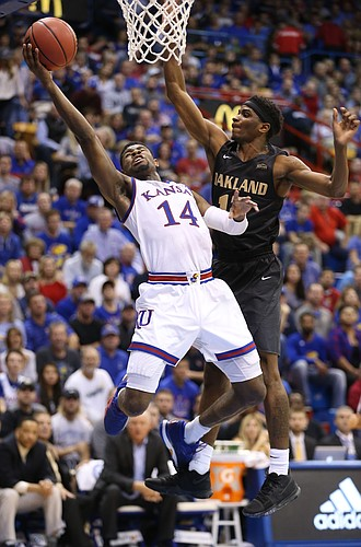 Kansas guard Malik Newman (14) gets in for a bucket past Oakland guard Stan Scott (12) during the first half on Friday, Nov. 24, 2017 at Allen Fieldhouse.