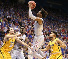 Kansas guard Devonte' Graham hangs for a shot during the first half on Tuesday, Nov. 28, 2017 at Allen Fieldhouse.