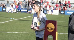 Lawrence High alumna Skylar Drum walks up to the podium after accepting her personalized NCAA Division II women's soccer national championship trophy following Central Missouri's win in penalty kicks over Carson-Newman on Saturday at Swope Soccer Village.
