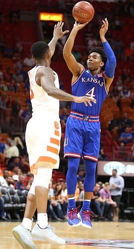 Kansas guard Devonte' Graham (4) puts up a three over Syracuse guard Frank Howard (23) during the second half, Saturday, Dec. 2, 2017 at American Airlines Arena in Miami.