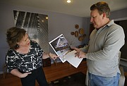In this AP File photo from March 29, 2013, Adlynn and Robert Harte share photos from the day of a police raid on their home in Leawood.