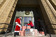 Graduate teaching assistants, David Cooper, left, Overland Park, Kan. and Sorcha Hyland, Lawrence, work to amass a pile of Christmas presents on the steps of Strong Hall before delivering them outside the office of the chancellor on Thursday, Dec. 7, 2017. The presents, carried messages asking members of the University of Kansas administration for improved compensation, benefits and resources. The group marched the presents from Ecumenical Campus Ministries to Strong Hall over the lunch hour.