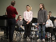 Free State High School students Harlee Crossett, center, and Gabriel Leverette, listen as Mike Meyer of Meyer Music notifies them that they are the recipients of new instruments through Meyer Music's Band of Angels program, Thursday, Dec. 7, 2017 in the auditorium at Free State High School.