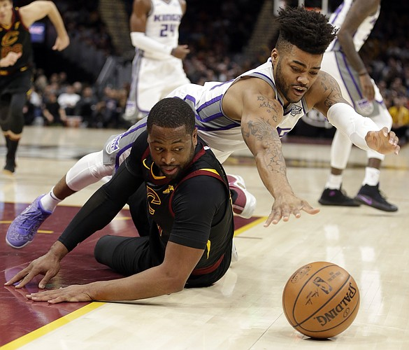 Sacramento Kings' Frank Mason III, right, and Cleveland Cavaliers' Dwyane Wade battle for a loose ball in the first half of an NBA basketball game, Wednesday, Dec. 6, 2017, in Cleveland. (AP Photo/Tony Dejak)