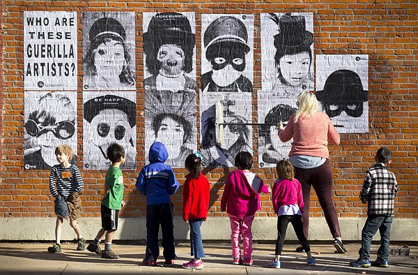 Young guerilla artists stand by as Rachel Van Wagoner, a studio assistant at the Lawrence Arts Center, brushes their guerilla artist portraits with wheat paste along the south wall of The Third Planet building at Ninth and Massachusetts streets on Friday, March 20, 2015. The students, who were participating in a guerilla art camp at the Lawrence Arts Center, were tasked to come up with an identity for themselves, but also to decide upon a positive message they wanted to share with the public.