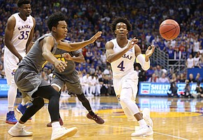 Kansas guard Devonte' Graham (4) throws a pass to the wing while defended by Arizona State guard Tra Holder (0) during the first half, Sunday, Dec. 10, 2017 at Allen Fieldhouse.