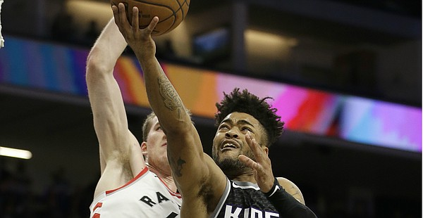 Sacramento Kings guard Frank Mason III, right, goes to the basket against Toronto Raptors center Jakob Poeltl, during the second half of an NBA basketball game, Sunday, Dec. 10, 2017, in Sacramento, Calif. The Raptors won 102-87. (AP Photo/Rich Pedroncelli)