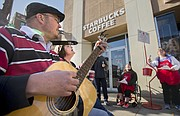 Seth Swartzendruber and Deana Bowen, para educators with Community Transitions, sing carols with program participants volunteering as bell ringers for the Salvation Army on Wednesday, Dec. 13, 2017 outside Starbuck's at the corner of Seventh and Massachusetts streets. For a two-hour span, the group sang and received donations for the Salvation Army, which is reporting lower numbers for donations this season.