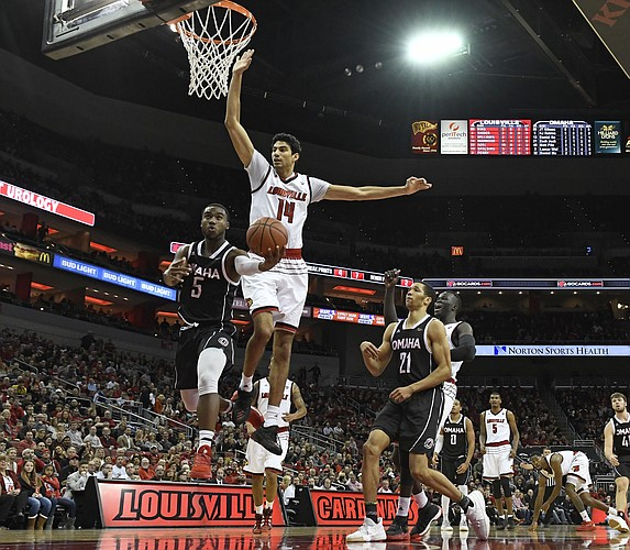 Omaha guard KJ Robinson (5) attempts a layup past the defense of Louisville forward Anas Mahmoud (14) during the first half of an NCAA college basketball game, Friday, Nov. 17, 2017, in Louisville, Ky.