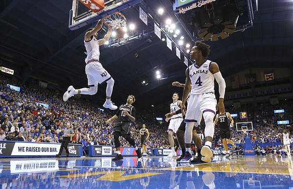 Kansas guard Sam Cunliffe (3) throws down a dunk off of a lob from Kansas guard Devonte' Graham (4) during the second half on Monday, Dec. 18, 2017 at Allen Fieldhouse.